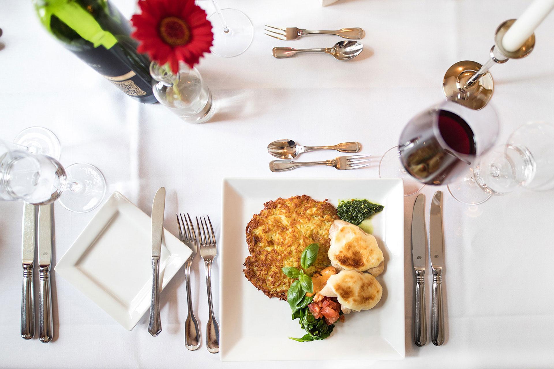 Röstiteller und Wein auf gedektem Tisch